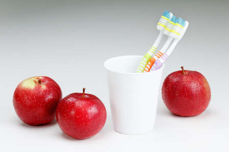 Toothbrush and apple, on white. healthy dental care concepts Фото со стока