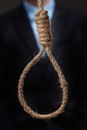 Hopeless depressed young man, is about to hang himself on the noose. Concept.