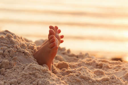 Closeup child kid feet on white sand beach. Sea on background, concept of a relaxing holiday on the coast Standard-Bild