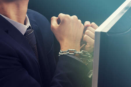 Hands of caucasian businessman addicted to internet and locked with iron chain wrists in smartphone internet addiction and slave to online network addict concept