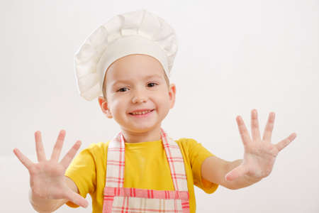 Details of children's hands kneading dough. Cheerful cook child boy in a cap prepares burritos or pizza Archivio Fotografico