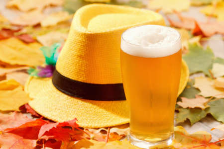 Beer glass pint octoberfest picnic on natural background with hat and autumn yellow leaves
