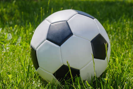 Traditional soccer ball on soccer field with green grass Stockfoto