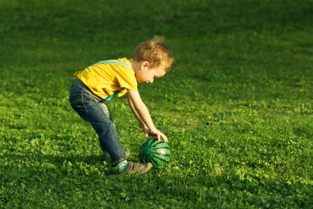 Cute positive kid, playing happily with ball on green meadow.