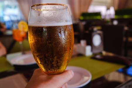 Beer in hand, cafe alcohol bar, restaurant cafe interior, table and chairs