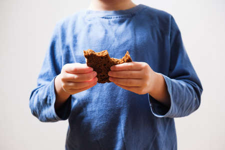 Child beggar eating cheap dirty bread. Poor children and people donations Volunteers Concept. Stock Photo