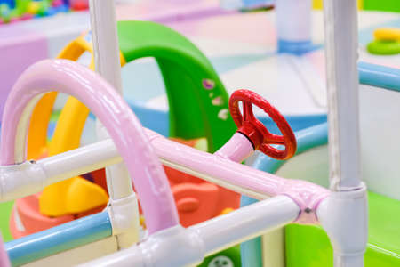 Children's steering wheel on a toy car in the playground amusement park Stock Photo