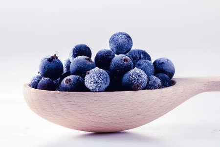 Mrożone jedzenie jagodowe i pyszny deser jagodowy w łyżce, na białym tle.