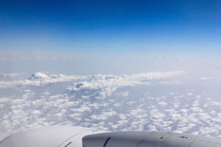 Unusual view of blue sky and clouds from a plane, top aircraft view