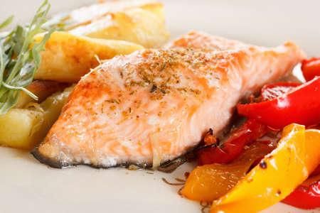 Filete de salmón preparado al horno con verduras, especias y rúcula en un primer plano de la placa