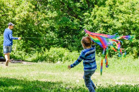 Deux frère caucasien qui longe la route forestière en cours d'exécution cerf-volant. Le concept de vacances actives d'été.