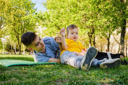 陽気な2人の兄弟は公園の草の上に横たわって、笑顔で面白いゲームで遊ぶ