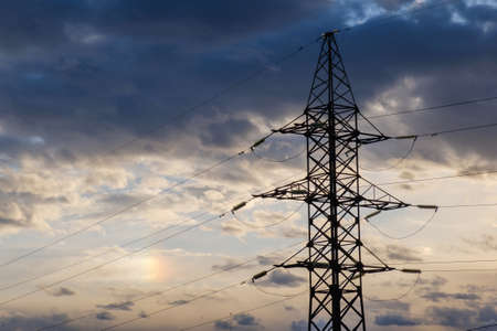 High voltage power pylons against blue sky and sun rays Stock Photo