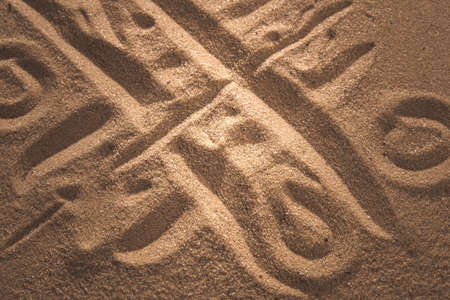 tic-tac-toe game drawing in sand background close up