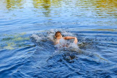 strong young man swiming in the sea over blue water
