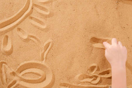 Sand art therapy, child's hands are painted on a table with sand Standard-Bild