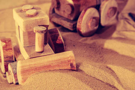 Toddler child hands playing with wooden toy tractor bulldozer model on sand of sea beach