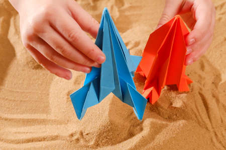 Happy child boy playing with handmade origami paper rocket on beach sand, start up concept