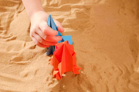 Happy child boy playing with handmade origami paper rocket on beach sand
