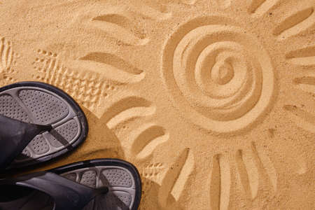 Slippers sands on the beach in the sand stuck to the sneakers with sun art
