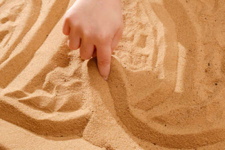 Sand art therapy, childs hands are painted on a table with sand