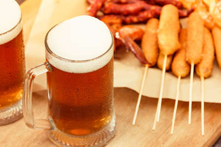Beer glass alcohol drink with food sausage and meat, pub view.