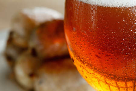 Traditional homemade coiled sausage with beer on wooden table