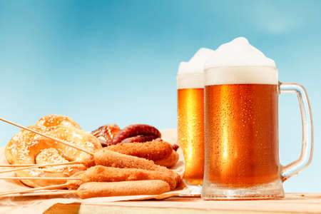 Beer glass alcohol drink with food sausage and meat, meal background.