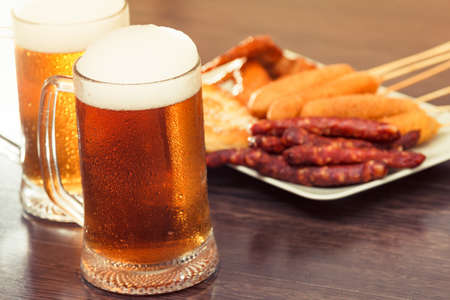 Beer glass alcohol drink with food sausage and meat, grilled top. Reklamní fotografie