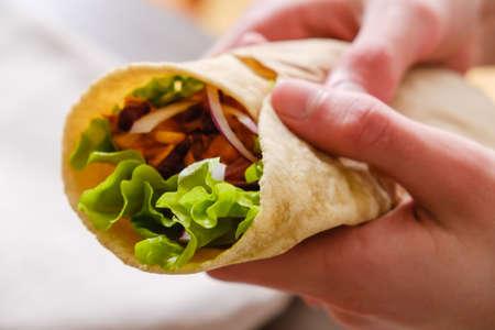 Mexikanischer Burrito mit Hühnchen, Gemüse, Pfeffer und Bohnen. Burrithos-Takos-Essen in der Hand. Straßen-Fastfood auf weißem Hintergrund Standard-Bild