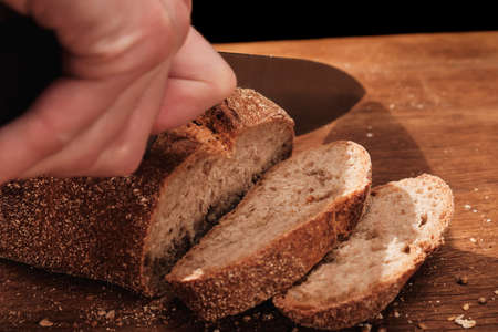 Chef cuts with a knife Whole Fresh fragrant bread on the table. Food concept Wheat pastry on cutting board