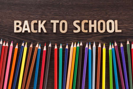 Colorful pencil crayons on a dark wooden background, Back to school