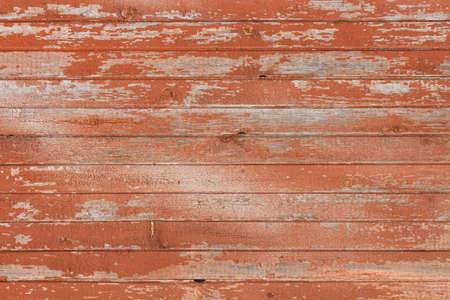 Background of old wooden board with peeling cracked red paint Imagens