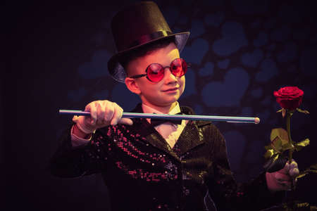 Magician kid illusionist boy in hat, magic show. illusion wizard isolated black background Stock Photo