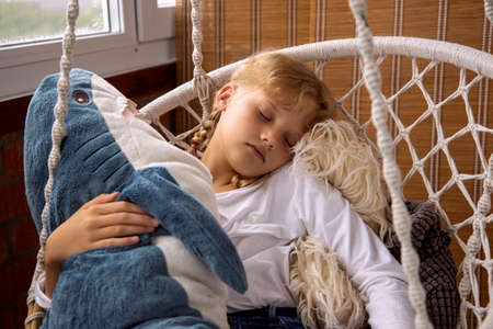The girl sleeps in a hammock with a plush toy. Toy shark 免版税图像