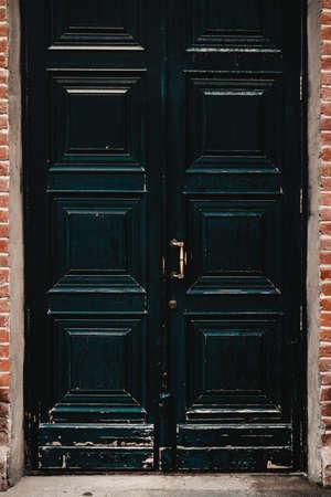 Vintage shabby black doors with gold handle on brick wall 免版税图像