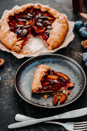 A piece of homemade plum pie on a black plate. Simple dessert with fruits, vertical photo. High quality photo