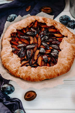 Sweet homemade pie with plums on a white table, vertical photo. High quality photo 版權商用圖片