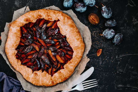 Sweet homemade pie with plums on a black background, top view, copy space. High quality photo