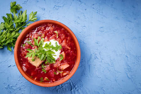Borscht with sour cream in earthenware dishes, top view - a dish of traditional Russian and Ukrainian cuisine. Free space for your text. High quality photo