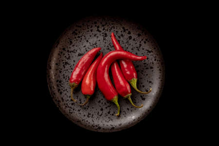 Red hot chili peppers on a black plate, top view. Isolated black background. High quality photo