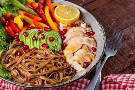 Healthy buddha bowl lunch - soba noodles with chicken, avocado and vegetables close-up. High quality photo