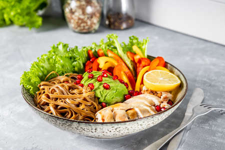 Healthy buddha bowl lunch - soba noodles with chicken, avocado and vegetables on the table. High quality photo Reklamní fotografie