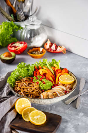 Healthy buddha bowl lunch - soba noodles with chicken, avocado and vegetables on the table, vertical photo. High quality photo