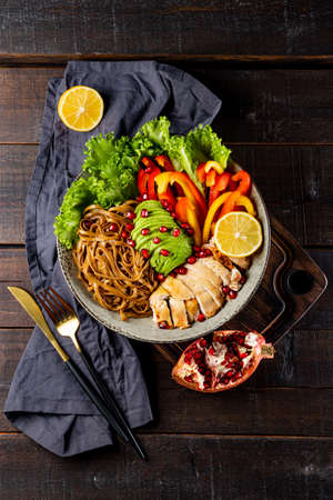 Healthy buddha bowl lunch - soba noodles with chicken, avocado and vegetables on a dark background, top view, vertical photo. High quality photo
