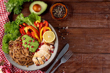 Healthy buddha bowl lunch - soba noodles with chicken, avocado and vegetables on a textured wooden background, top view, free space for your text. High quality photo Banque d'images