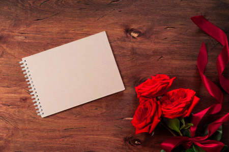Bouquet of red roses and a blank notepad on a textured wooden background, free space for text