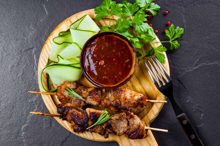 Grilled pork skewers with cucumber salad and barbecue sauce top view