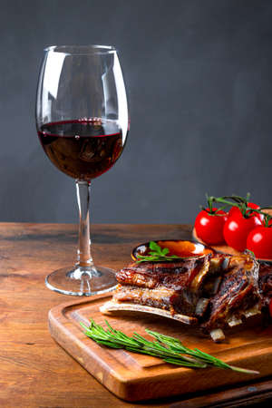 Grilled ribs in barbecue sauce and a glass of red wine on the table vertical photo
