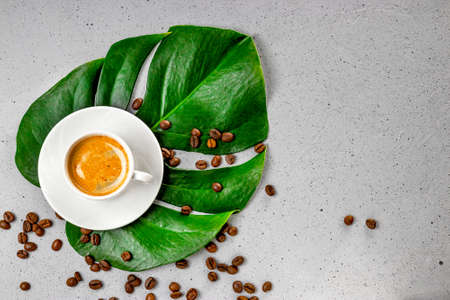 Cup of black coffee and coffee beans on monstera leaf and gray concrete background top view. High quality photo